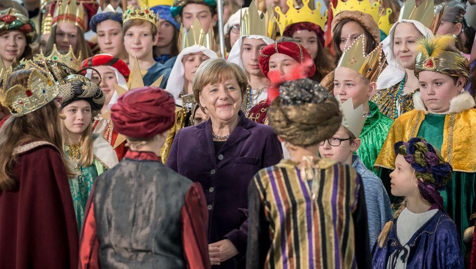 Kanzlerin Merkel zwischen Sternsingern im Bundeskanzleramt: Spenden für Kinder in Not