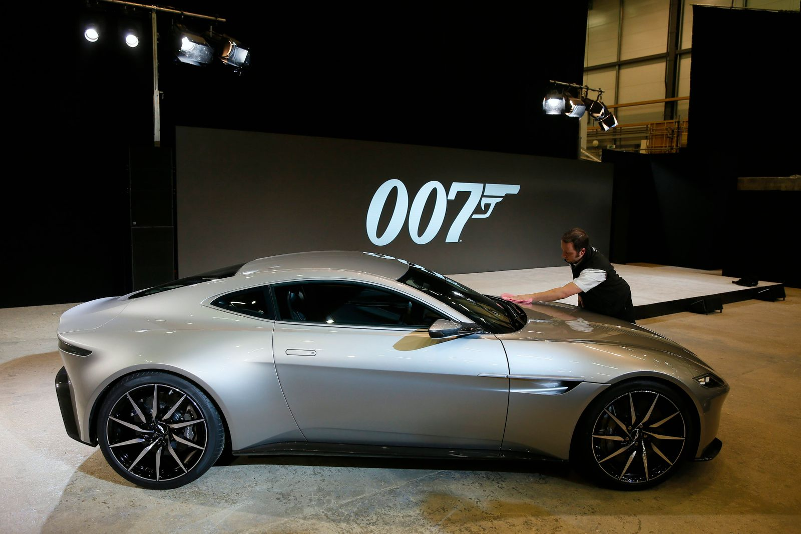 """A worker polishes an Aston Martin DB10 car during an event to mark the start of production for the new James Bond film """"Spectre"""", at Pinewood Studios"""