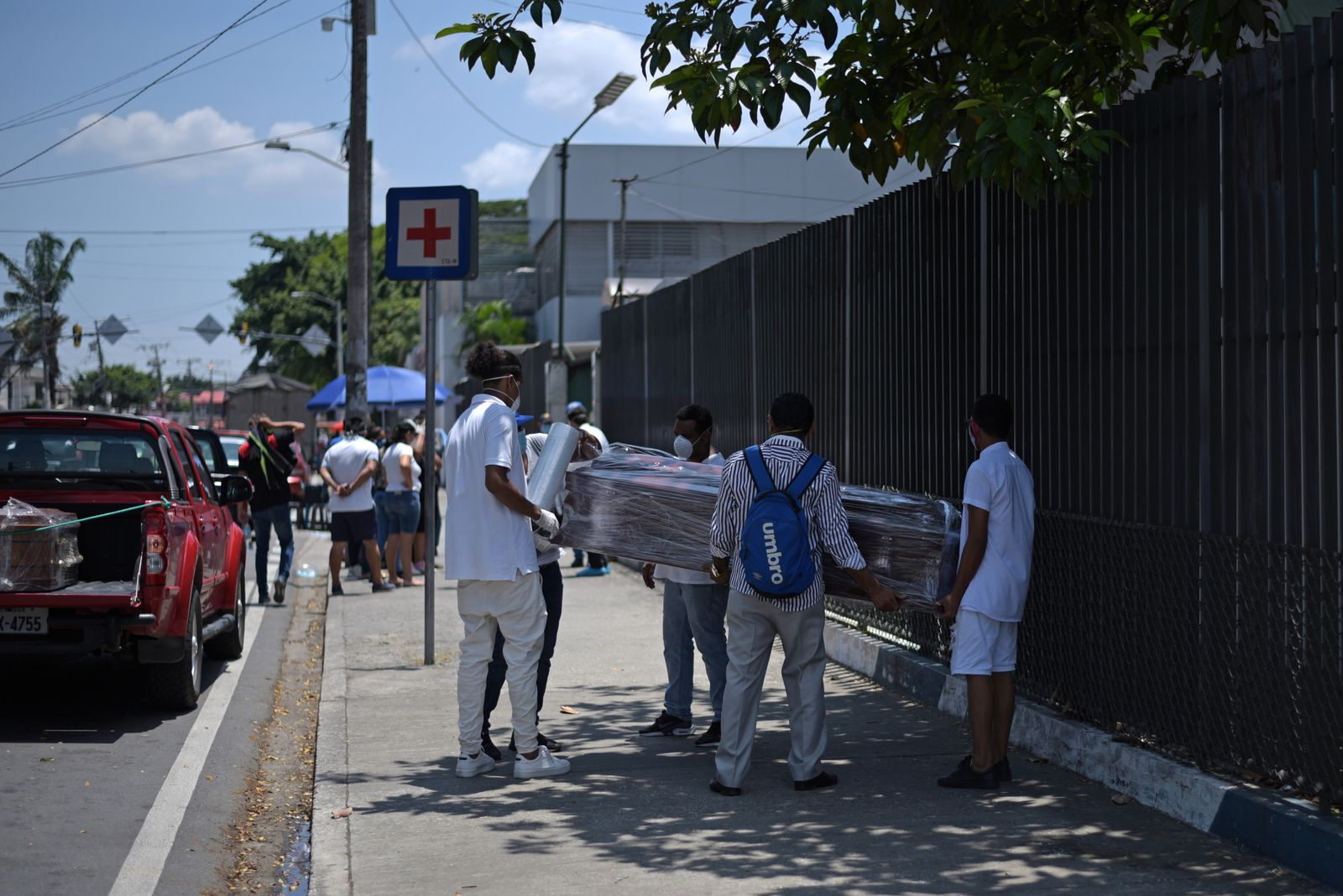 People wrap a coffin with plastic sheeting outside of Teodoro Maldonado Carbo Hospital amid the spread of the coronavirus disease (COVID-19), in Guayaquil