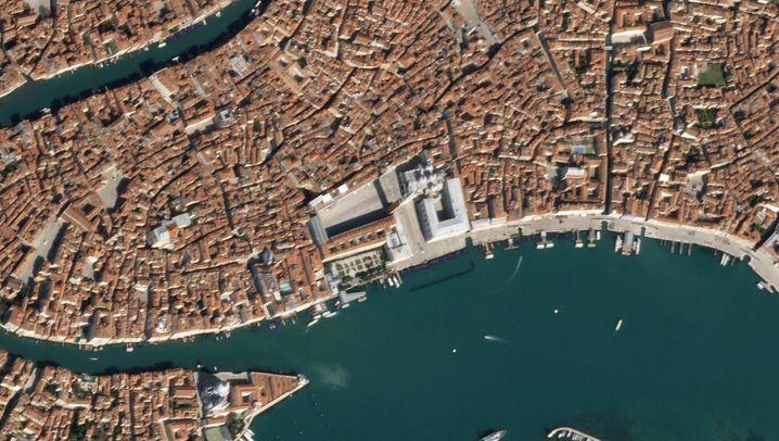 Satellitenbild des Stadtzentrums von Venedig (18. März 2020/20. Oktober 2019):Markusplatz mit Campanile, der Markusdom und der Dogenpalast - die bekanntesten Attraktionen der italienischen Lagunenstadt sorgen auch für den größten Andrang von Touristen, unabhängig von der Jahreszeit. Durchschnittlich etwa 90.000 Touristen besuchen Venedig täglich (bei etwas mehr als 50.000 ständigen Einwohnern), so viele, dass die Stadt seit Jahren eine Eintrittsgebühr für Touristen überdenkt. Am 8. März 2020 wurde Venedig zur roten Zone erklärt, seitdem kommen keine Besucher mehr, um die Sehenswürdigkeiten zu betrachten. Das Wasser der Kanäle erscheint klar wie lange nicht mehr, was hauptsächlich am momentan fehlenden Bootsverkehr liegt, der normalerweise das Sediment am Lagunengrund aufwirbelt. Berichte über die Rückkehr von Delfinen stellten sich als fake heraus. Immerhin: Die Einführung des Eintrittsgeldes wird wegen der Coronakrise erneut verschoben.
