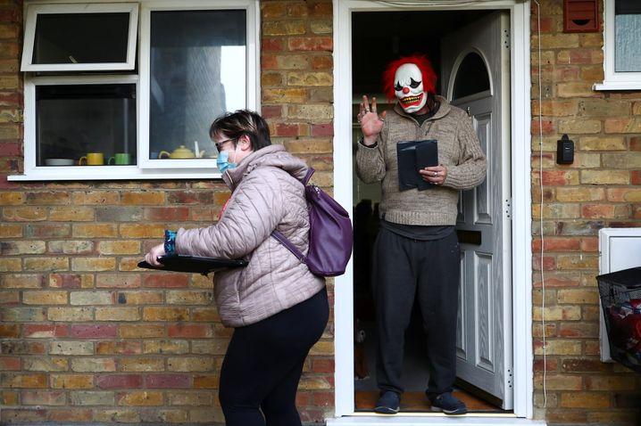 Bei einer Verteilaktion von Corona-Testkits in Großbritannien öffnet ein Mann die Tür in Clownsmaske