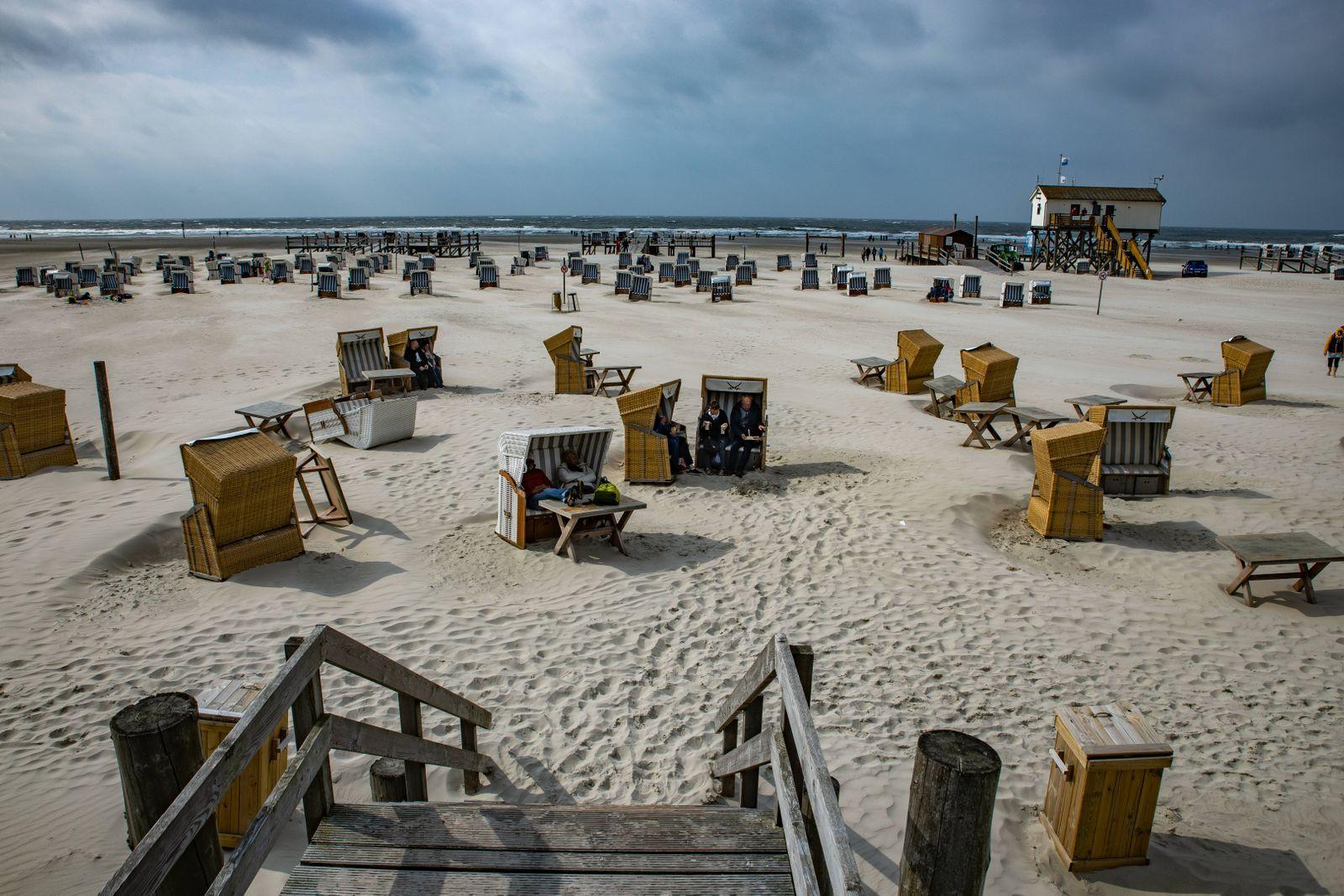 Trotz windigem Herbstwetter sind zahlreiche Menschen am Strand von St Peter Ording um an der Nordsee das Naturschauspiel