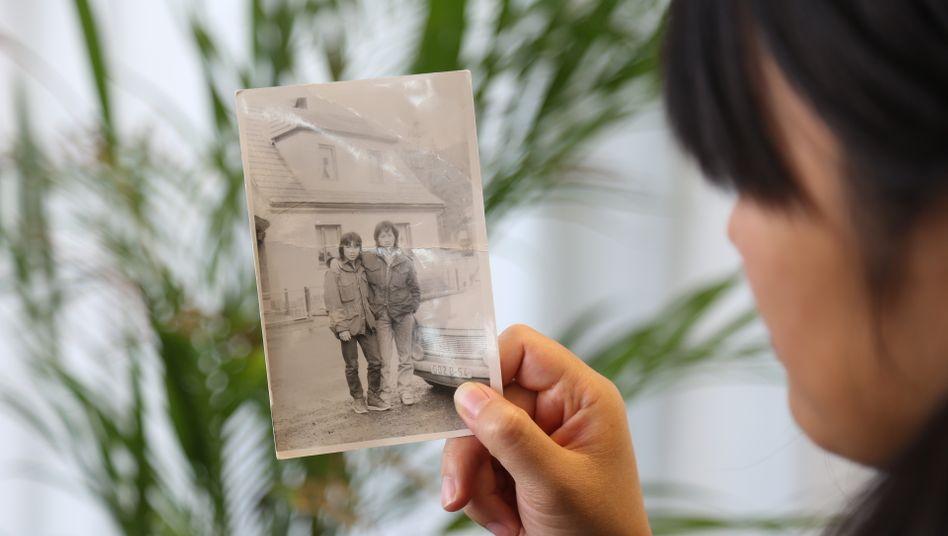 Autorin betrachtet alte Dokumente ihrer Eltern.