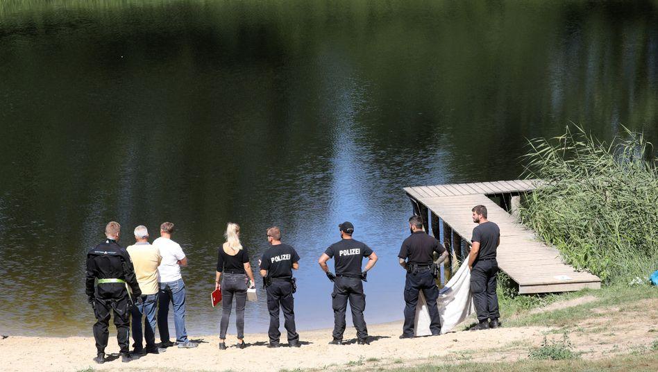 Polizisten stehen am Ufer des Sees, in dem ein siebenjähriger Junge umkam