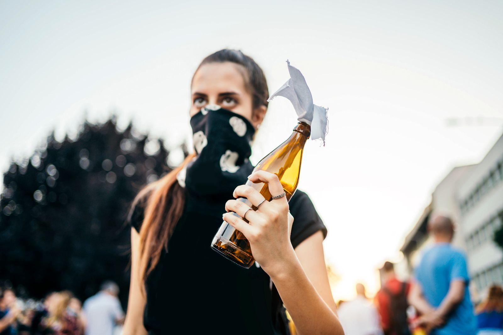 Young female protester with Molotov cocktail