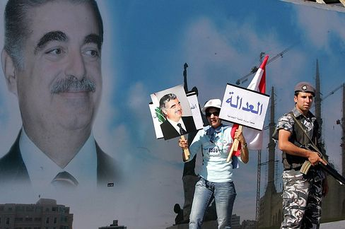 """A Lebanese demonstrator holds a portrait of ex-prime minister Rafiq Hariri and a sign reading """"justice"""" in Arabic."""