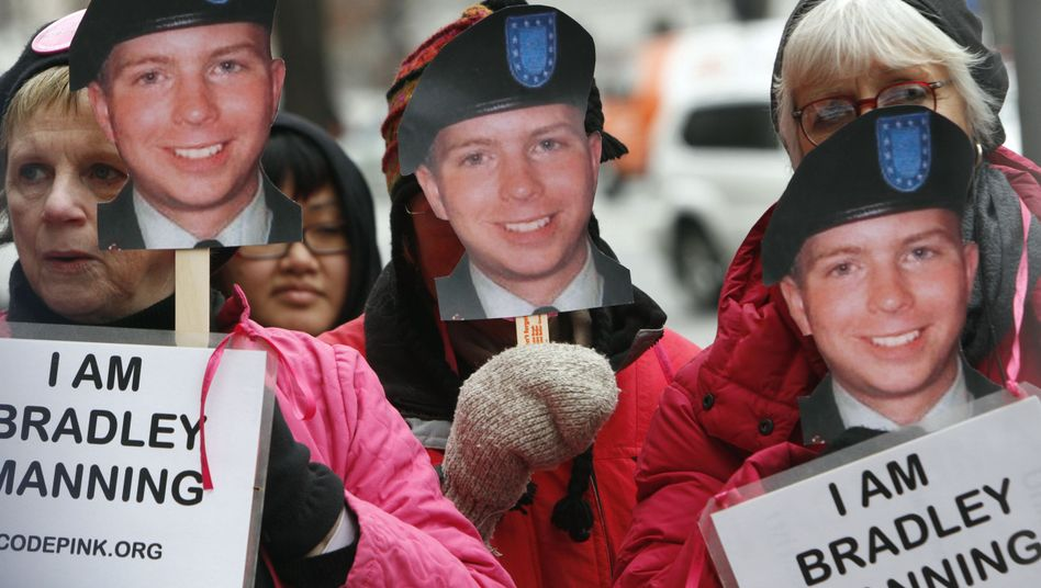 Activists hold signs in support of U.S. Army Pfc. Bradley Manning.