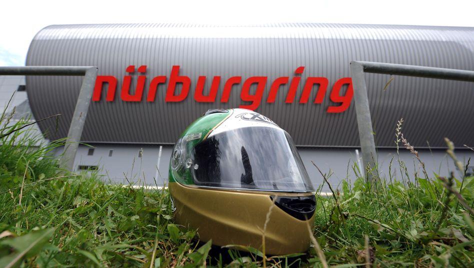 Helm vor Nürburgring-Schriftzug: Dominante Rolle des Landes Rheinland-Pfalz