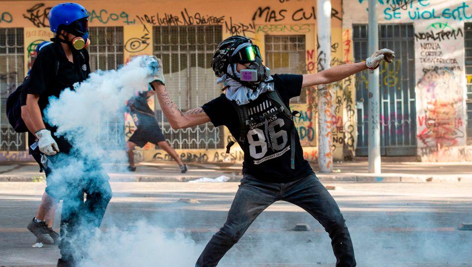 Ein Demonstrant wirft eine Tränengasgranate zurück in Richtung der chilenischen Polizei