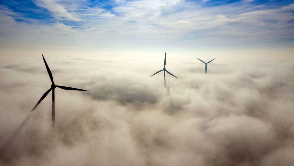 Windkraftanlagen ragen in Nordrhein-Westfalen aus dem Morgennebel