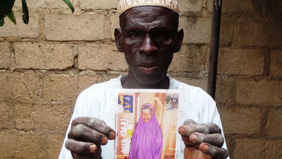 """Sani Garba, Vater des getöteten Bräutigams, mit einem Bild seiner Schwiegertochter Wasila Tasi'u: """"Wir können ihr nicht vergeben"""""""