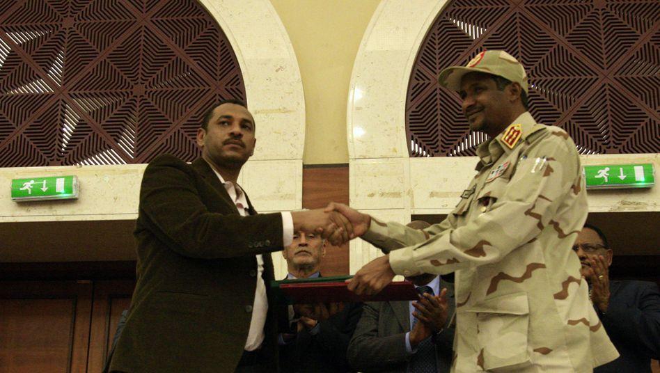 Handschlag, aber kein Blickkontakt: Ahmad al-Rabiah von der Friedensallianz und der gefürchtete General Hemedti