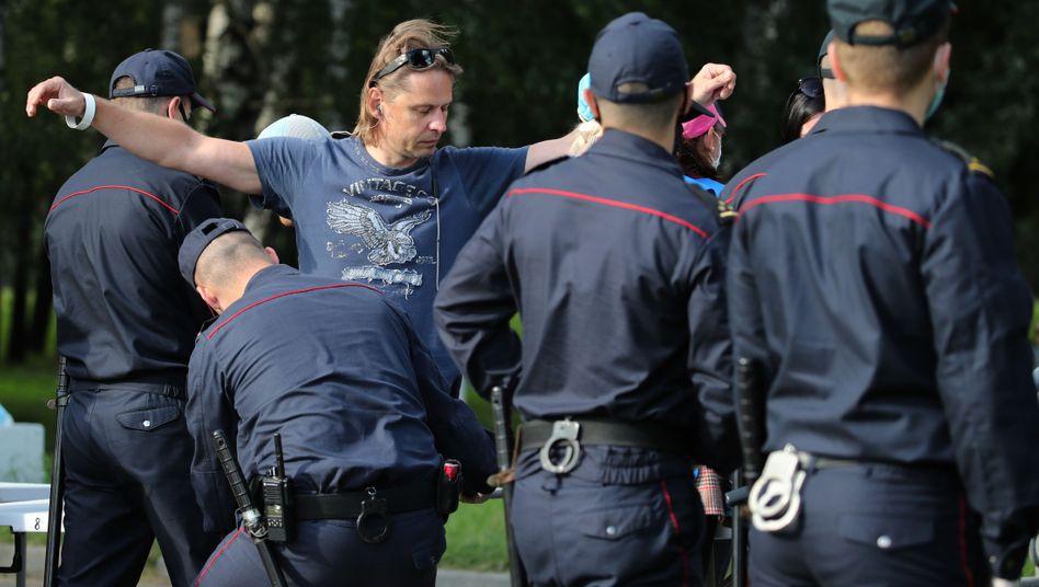 Belarussische Polizisten kontrollieren einen Mann, der auf eine Oppositions-Kundgebung möchte