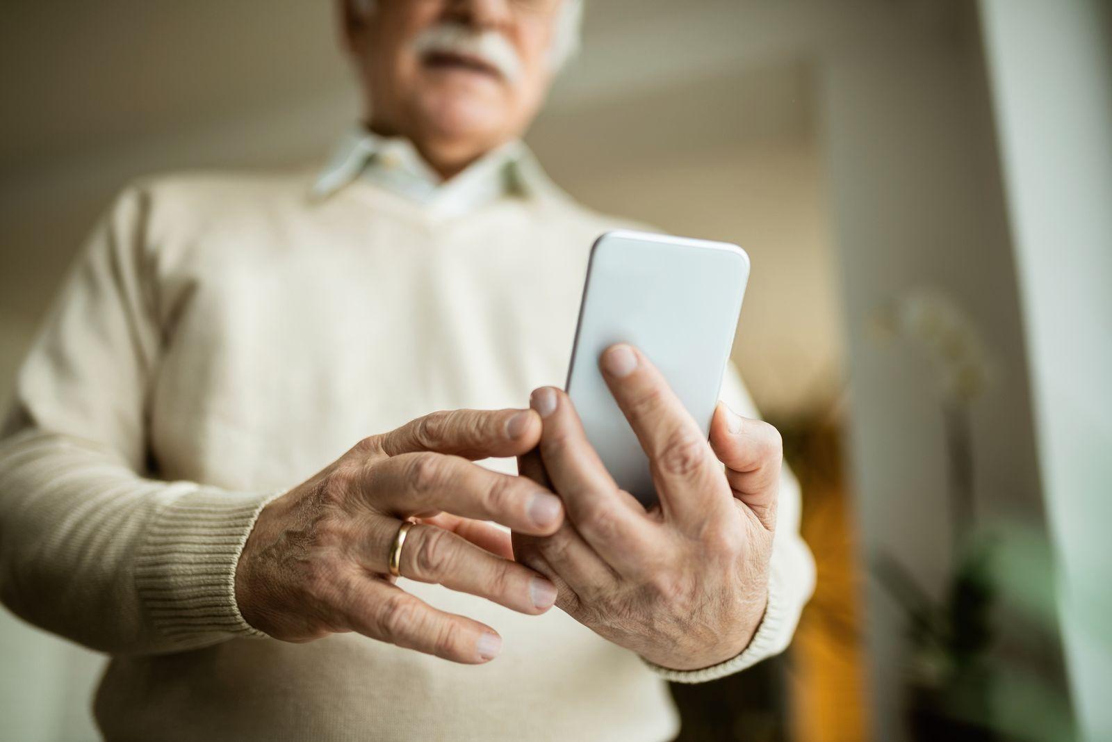 Close-up of mature man using smart phone.