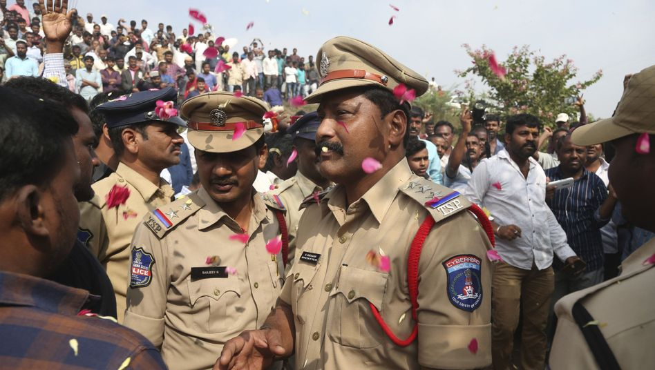 Menschen werfen Blütenblätter auf indische Polizisten, die den Tatort bewachen