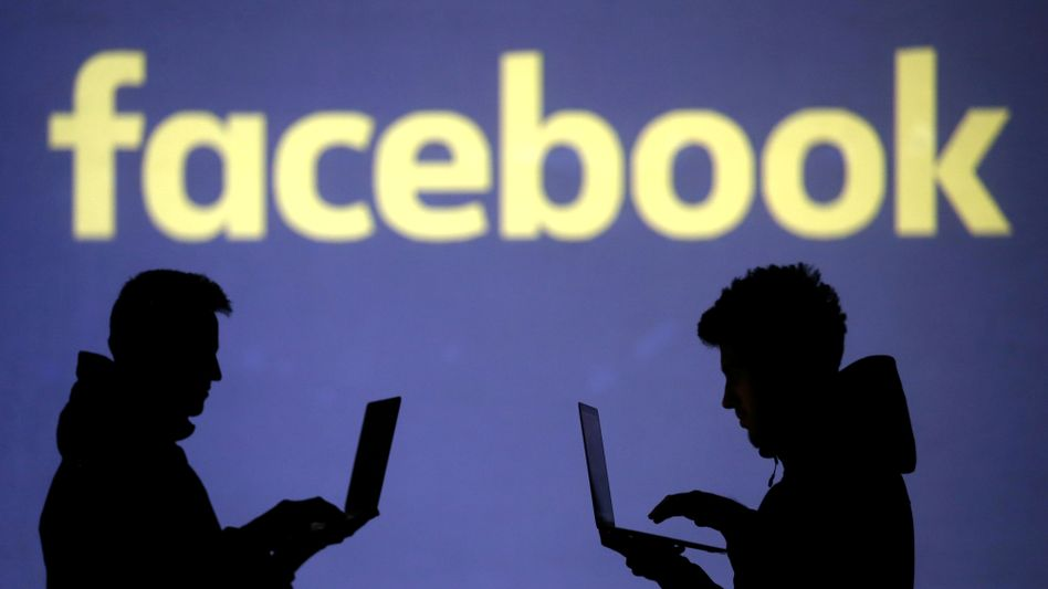 Menschen arbeiten vor Facebook-Logo - Symbolbild