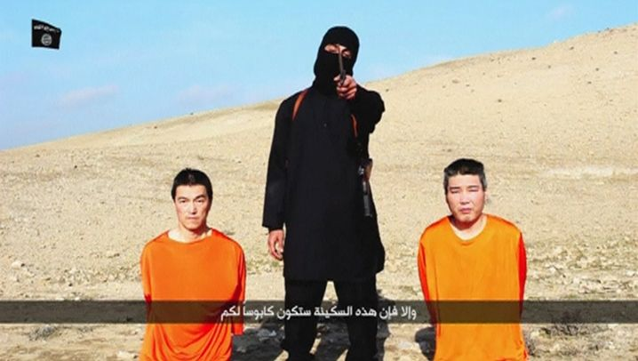 A screenshot from an Islamic State propaganda video shows two Japanese hostages in orange jumpsuits.