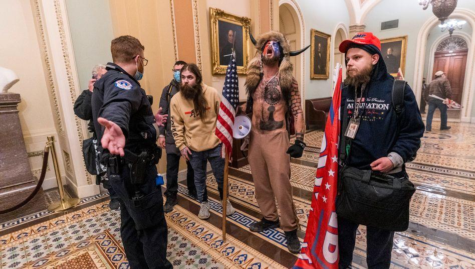 Beamter der Capitol Police mit Anhängern von Donald Trump im Inneren des Kapitols (am 6. Januar)