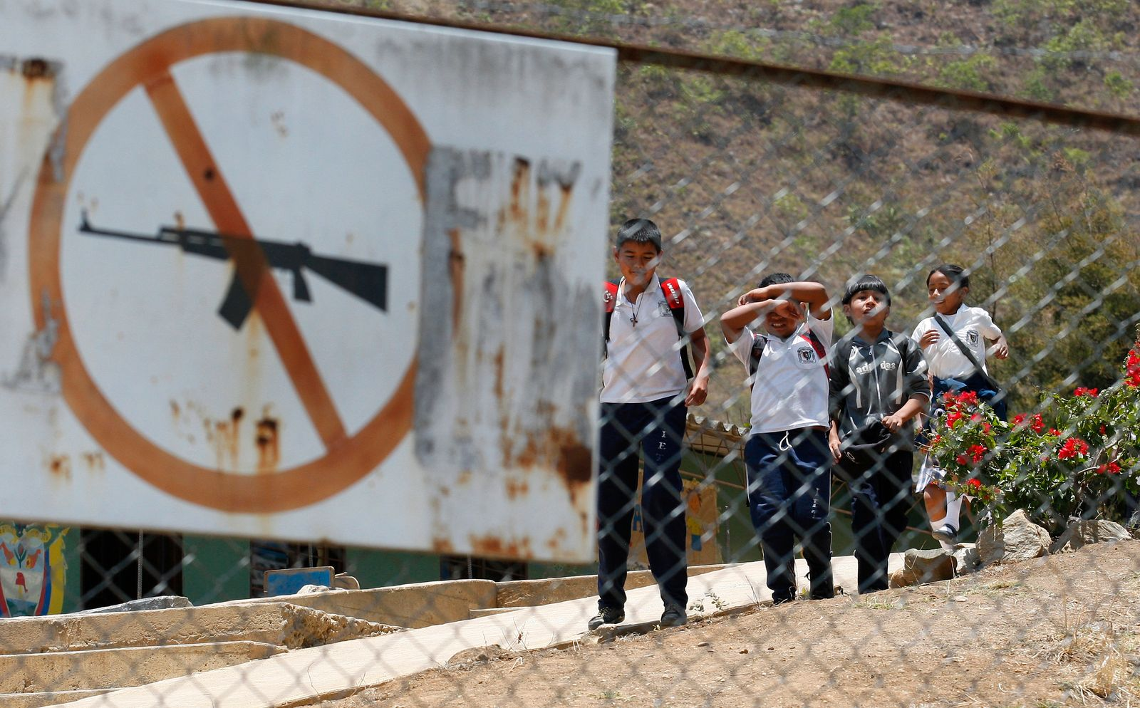 School children walk behind a sign prohibiting weapons at a school in Toribio