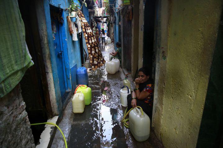 Frauen sammeln in einem Slum in Mumbai, Indien, Wasser in Kanistern