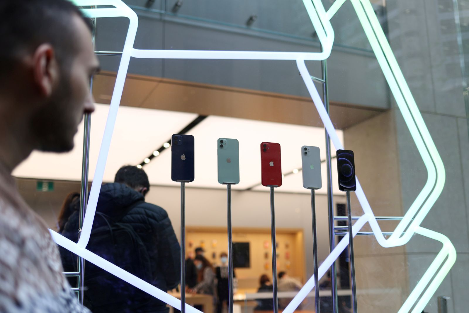 FILE PHOTO: A shopper looks at an iPhone 12 display while waiting in line to enter an Apple Store in Sydney