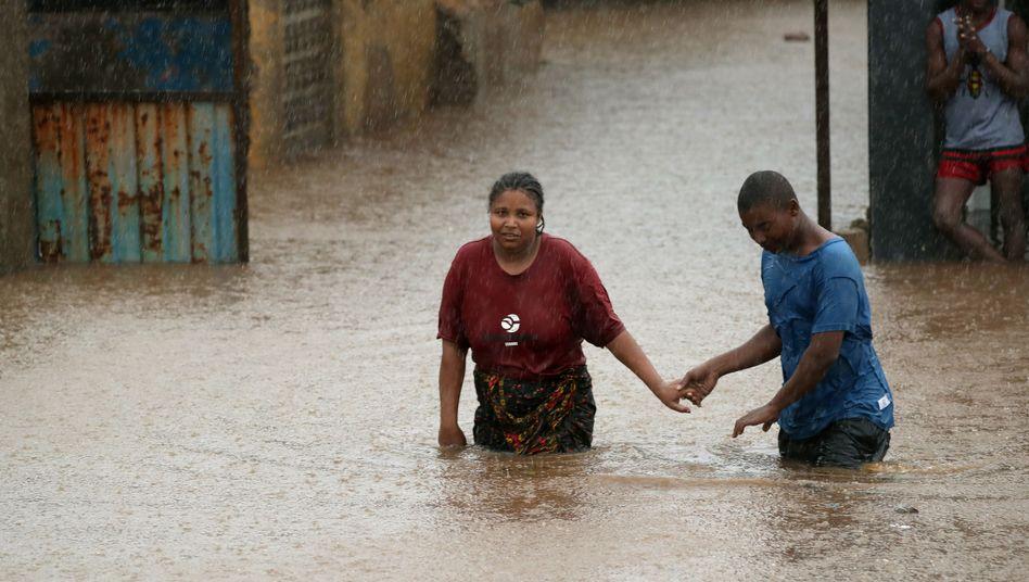"""Bewohner der Stadt Pemba, Mosambik, waten durch die Wassermassen des Sturmsystems """"Kenneth"""""""