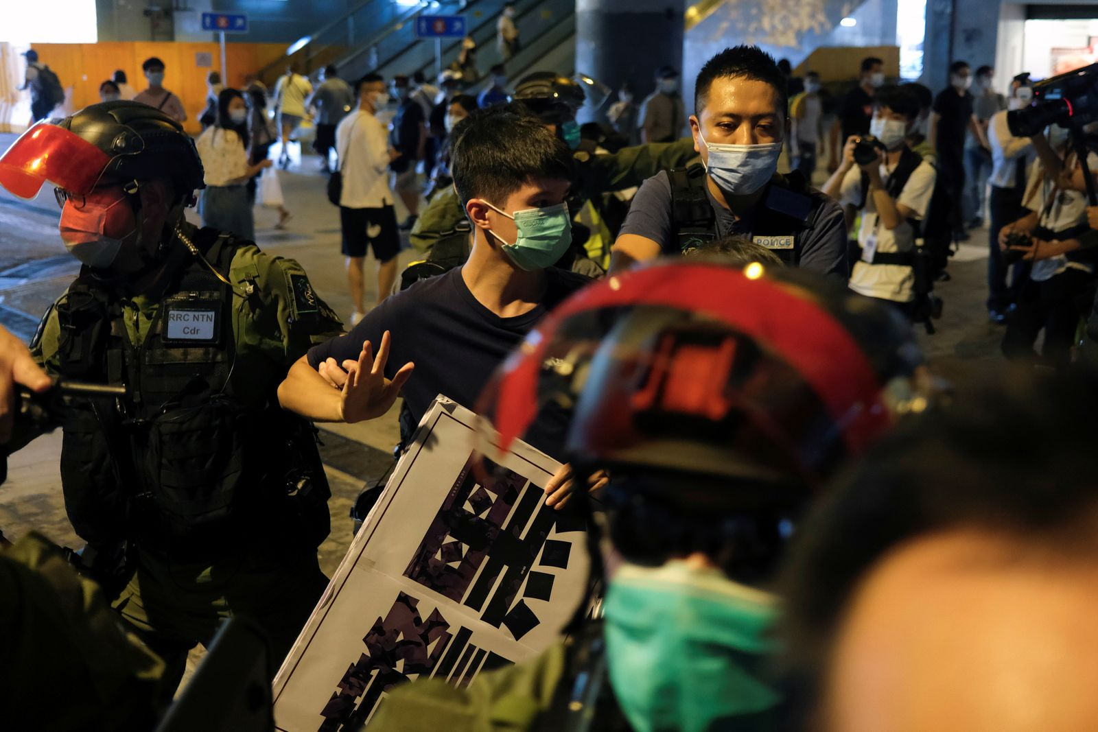 Police take away a protester to avoid people to gather to mark the anniversary of the attack by more than 100 white-wearing men with pipes and poles on July 21 last year, at Yuen Long, in Hong Kong