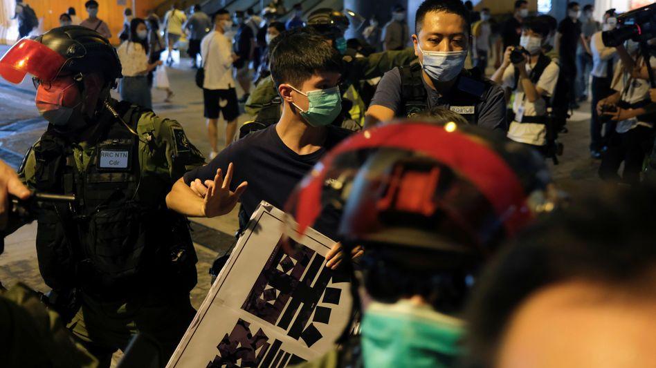Polizisten führen in Hongkong einen Demonstranten ab
