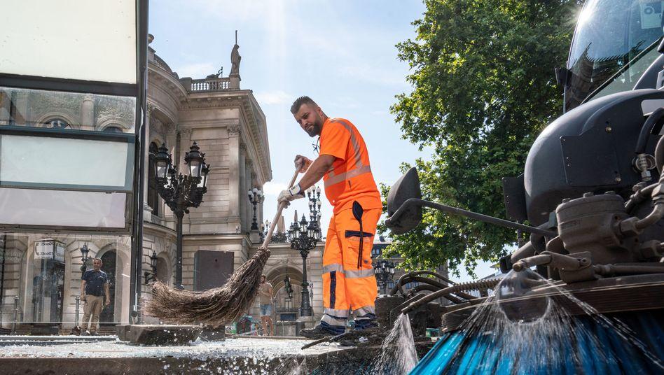 Aufräumarbeiten nach den Krawallen: Mitarbeiter der Stadtreinigung vor der Alten Oper in Frankfurt