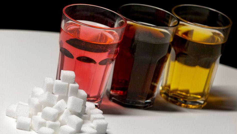 Gläser gefüllt mit roter Limonade, Cola und einem Energy-Drink