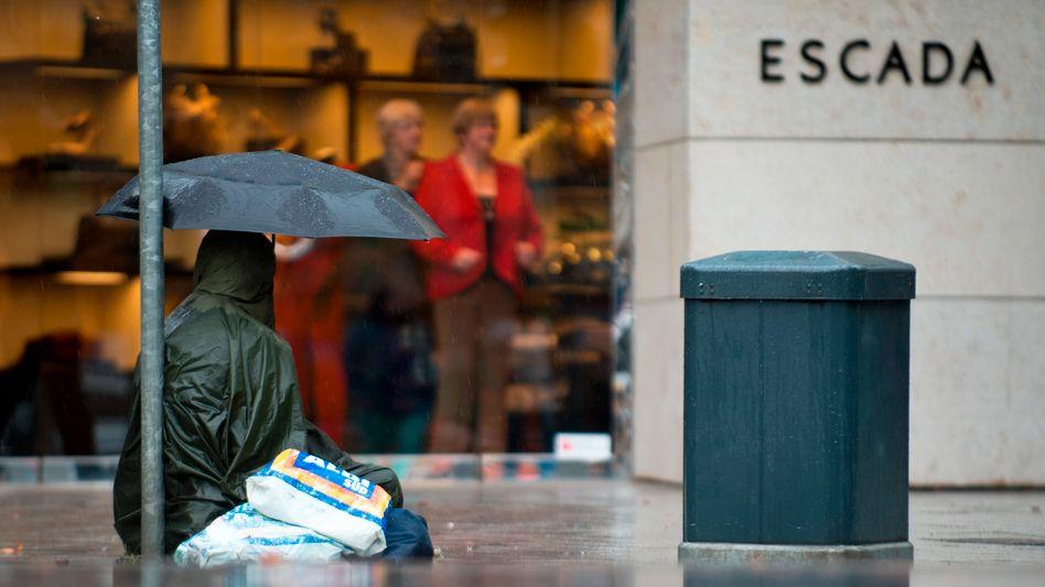Ein Bettler mit Regenschirm auf der Düsseldorfer Königsallee