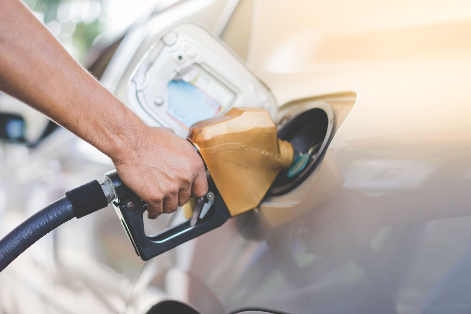 Close-Up Of Hand Refueling Car