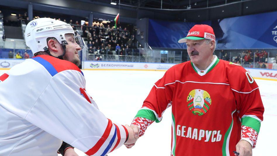 """Händeschütteln trotz Corona: Präsident Alexander Lukaschenko (r.) Ende März: """"Auf dem Eis gibt es keine Viren"""""""