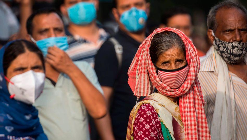 Menschen in Delhi tragen Masken zum Schutz vor dem Coronavirus