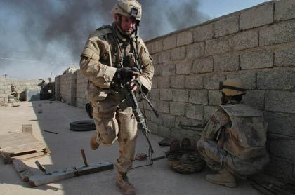 Escalating costs of war: A U.S. soldier runs for cover in the northern Iraq town of Tal Afar, September 2005.