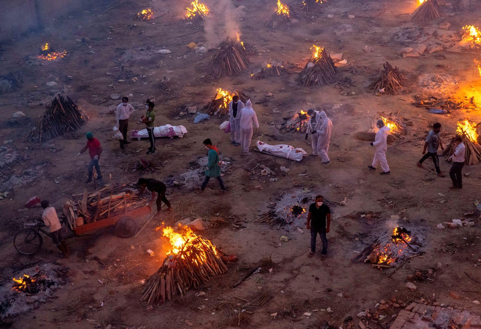 People wait to cremate COVID-19 victims at a crematorium ground in New Delhi