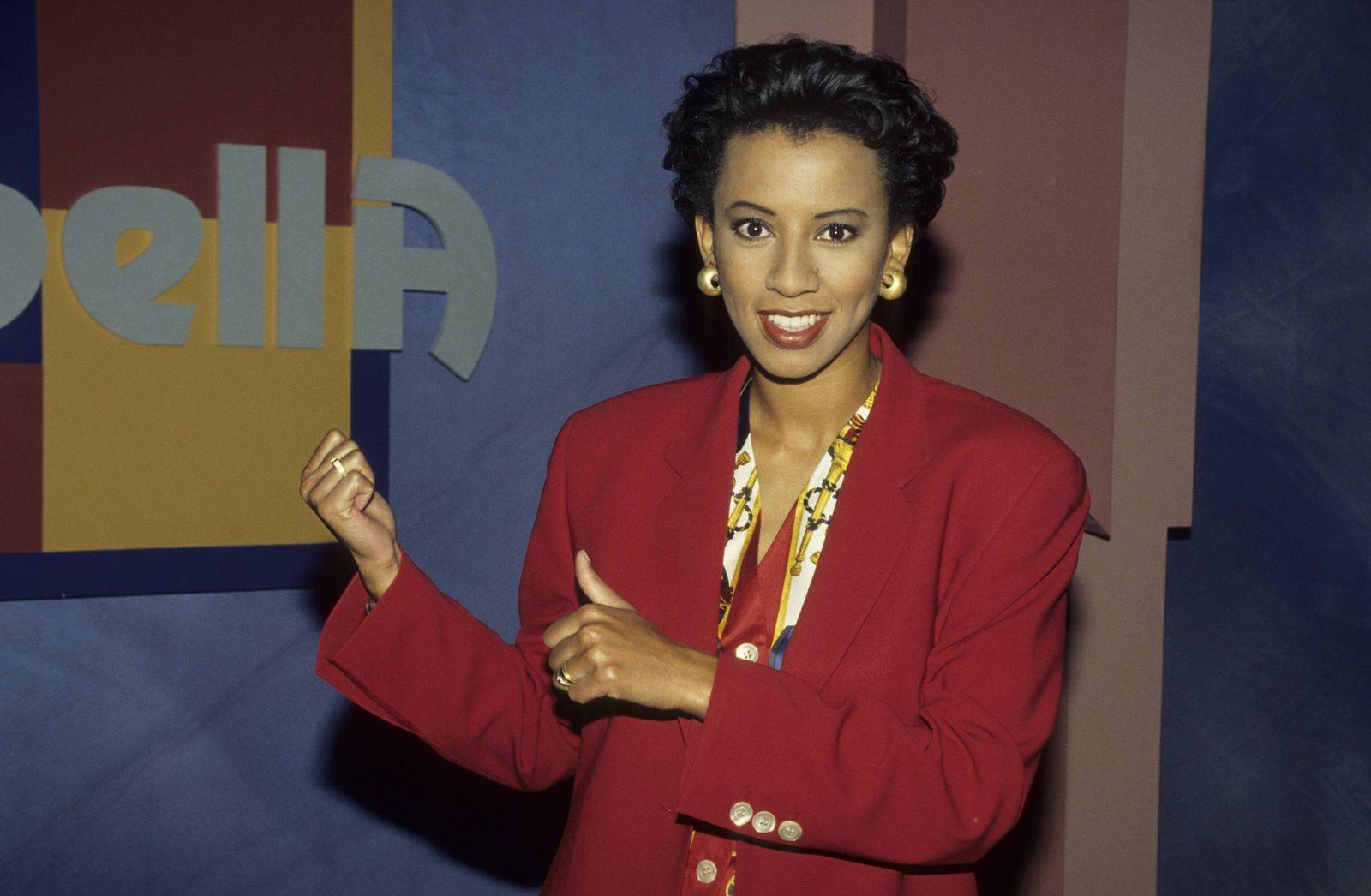 Arabella Kiesbauer 02/94 kück quer halb Logo lächelnd Kulisse seriös Blazer rot Frau Fernsehen Moderation Journalismus