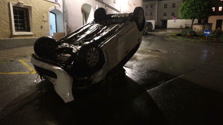 Ein Auto liegt im österreichischen Hallein kopfüber auf der Straße