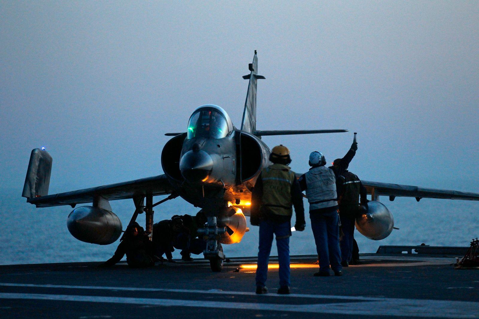 Flight deck crew work around a Super Etendard fighter jet aboard the Charles de Gaulle aircraft carrier