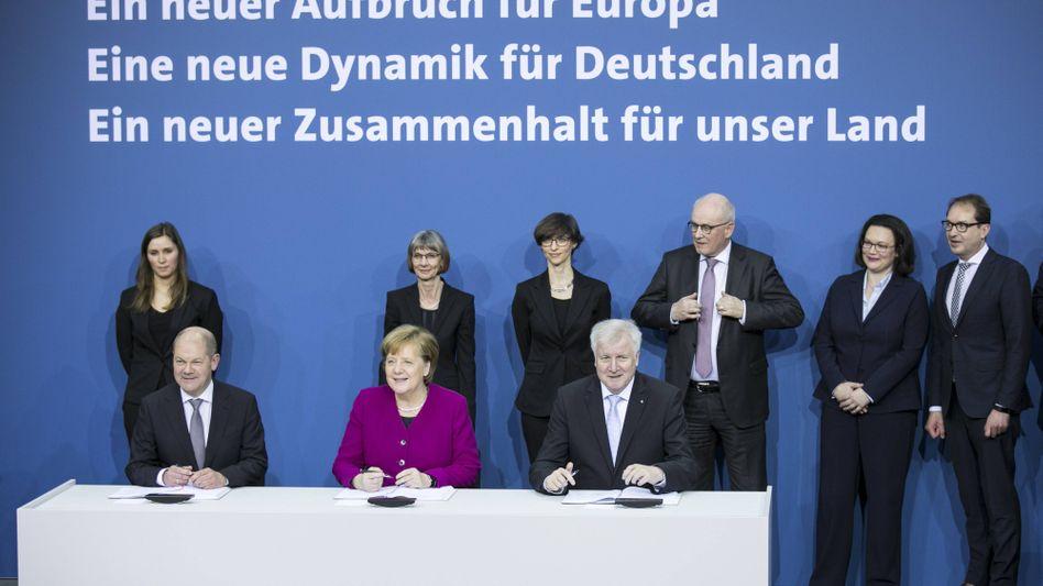 Damalige Parteichefs Olaf Scholz (SPD), Angela Merkel (CDU) und Horst Seehofer (CSU) (v.l.) bei der Unterzeichnung des Koalitionsvertrages am 12. März 2018