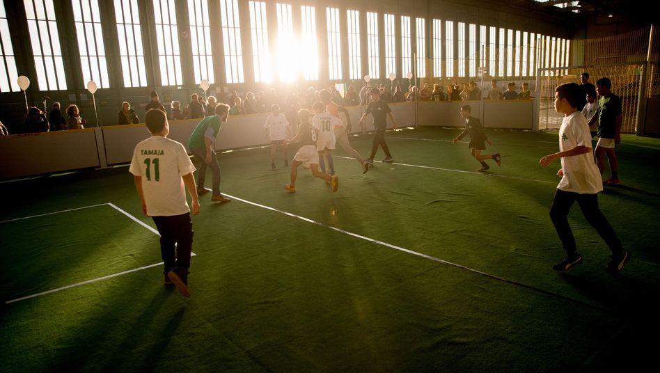 Flüchtlingskinder spielen in einer Notunterkunft Fußball