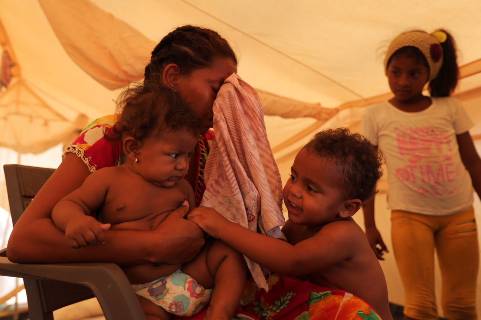 A Venezuelan migrant mother cries while carrying her baby, inside a tent in a camp run by the UN refugee agency UNHCR in Maicao