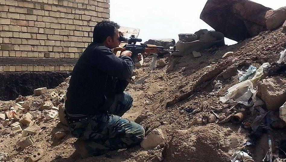 Ein Mitglied der irakischen Sicherheitskräfte richtet sein Gewehr auf Stellungen des IS: Massenhinrichtungen von irakischen Soldaten