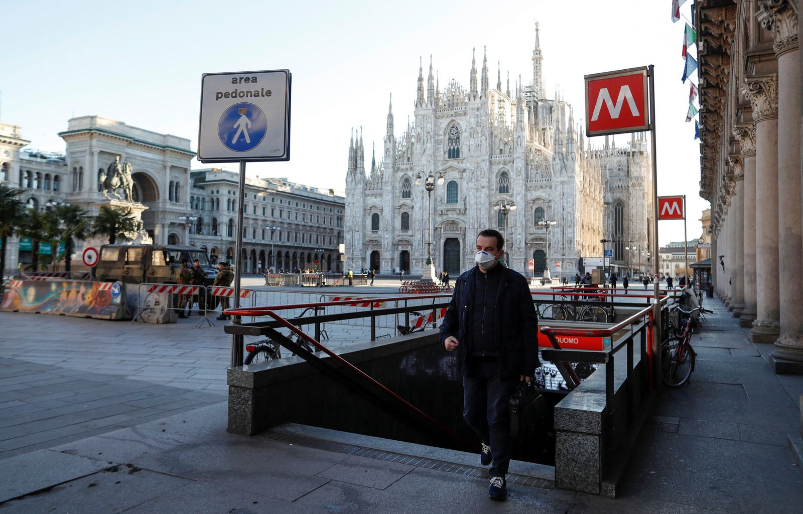 A man wearing a protective face mask walk next to a near-empty Duomo square, usually full of people, as a coronavirus outbreak in northern Italy continues to grow, in Milan