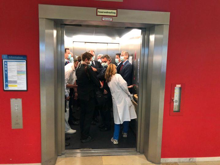 Spahn, Bouffier und weitere Menschen in einem Fahrstuhl der Uniklinik Gießen