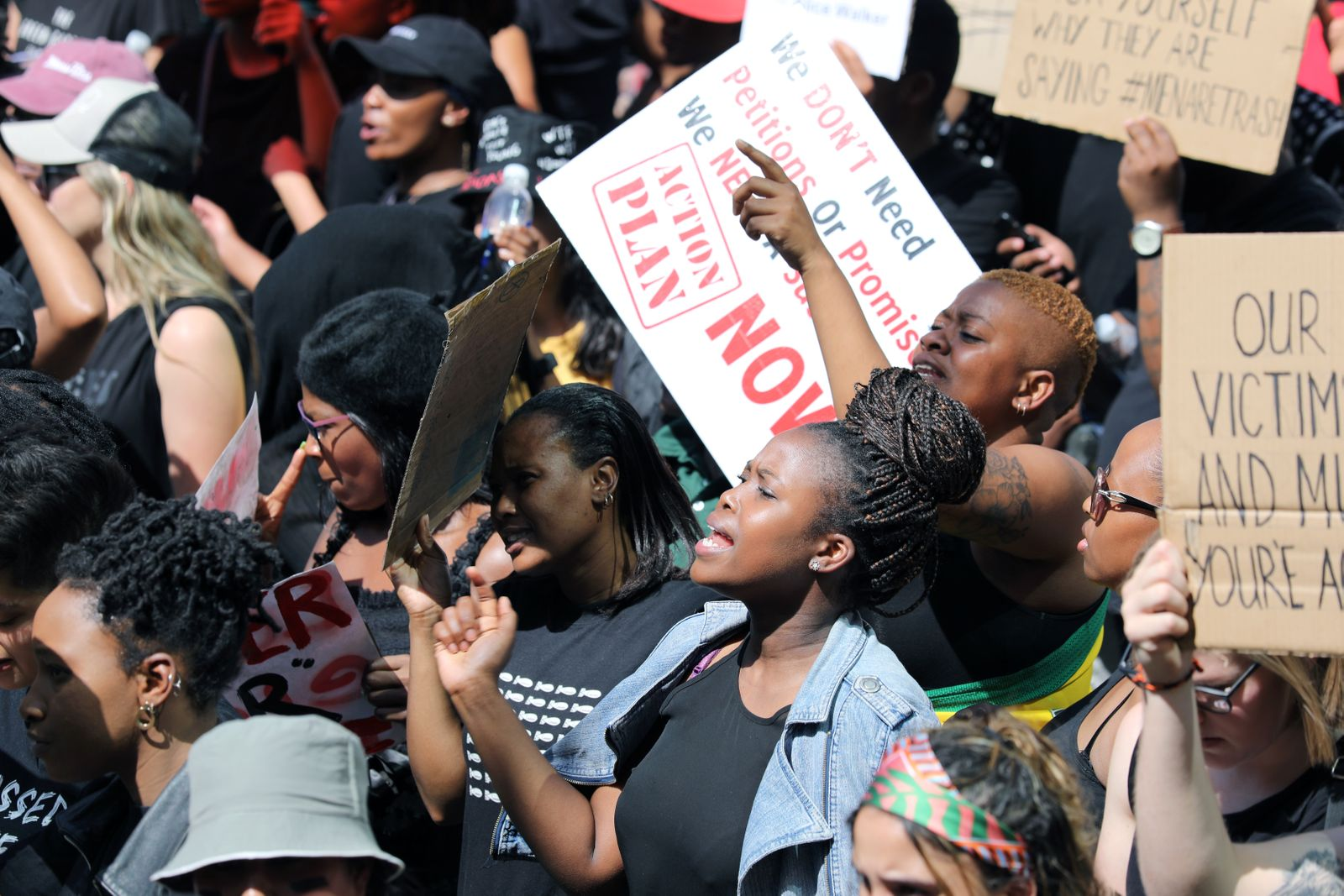 Women hold placards as they protest against gender-based violence, outside the Johannesburg Stock Exchange in Sandton, Johannesburg