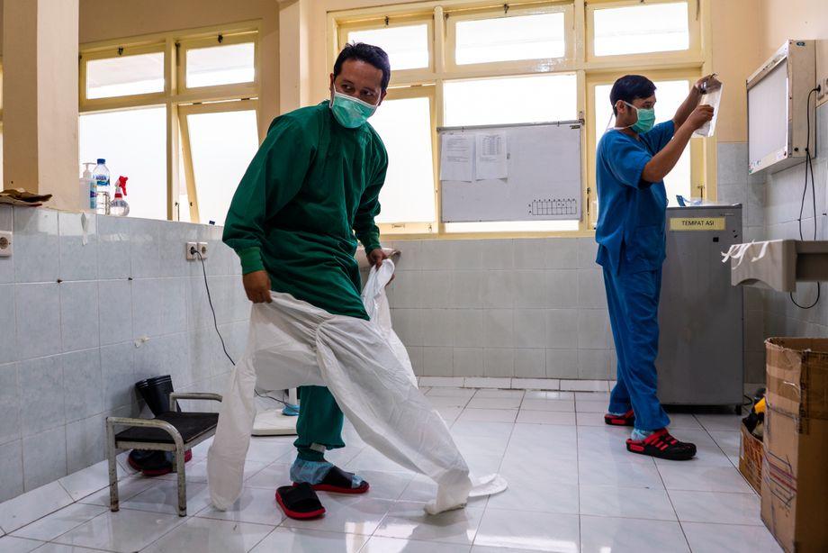 Perawat Hiro dan Fanny mengenakan alat pelindung sebelum merawat pasien Covid di bangsal isolasi