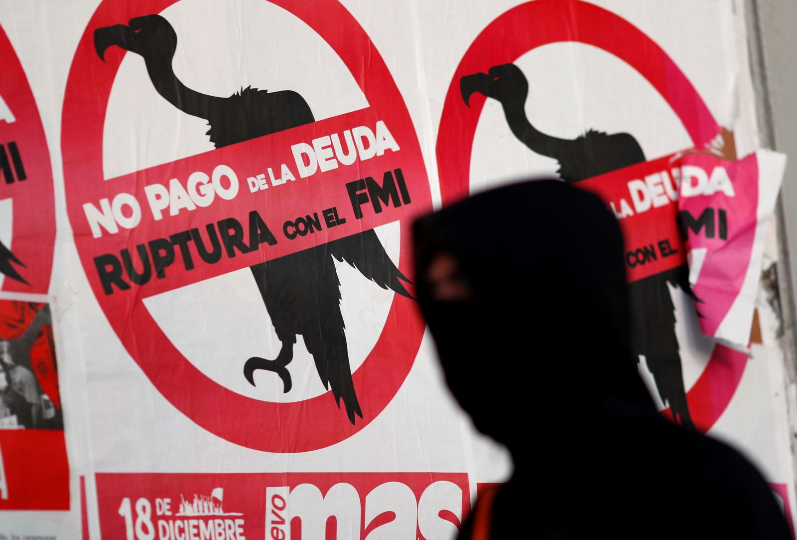 """FILE PHOTO: A pedestrian wearing a face mask walks past posters on the street that read """"No to the payment of the debt. Break with the IMF"""", in Buenos Aires"""