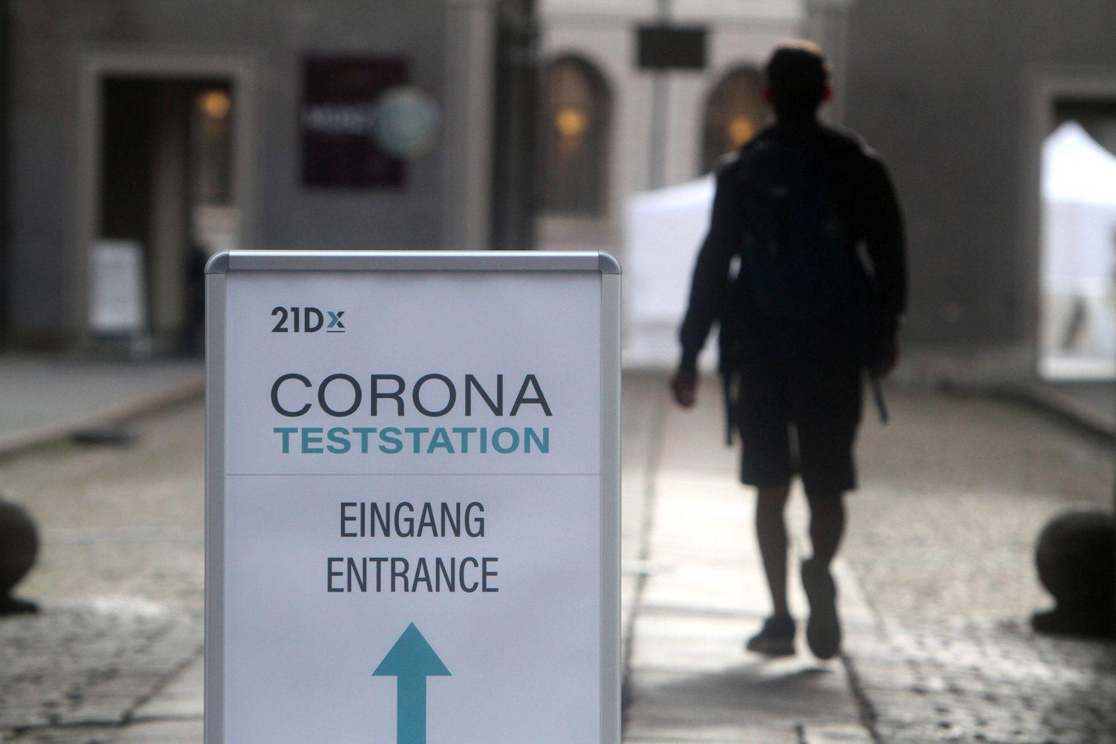 Aufsteller mit Richtungspfeil und Aufschrift 21D Corona Teststation steht in der Innenstadt von München. Ein Mann geht z