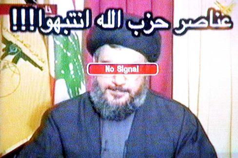 """Fernsehbild mit Hisbollah-Chef Hassan Nasrallah: Israel hat eine Botschaft in arabischer Schrift eingeblendet. """"Mitglieder der Hisbollah. Seid auf der Hut!"""", heißt es dort."""